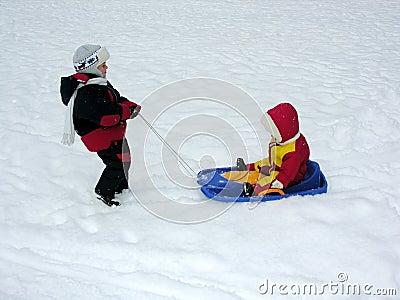 Boy ride baby on sled