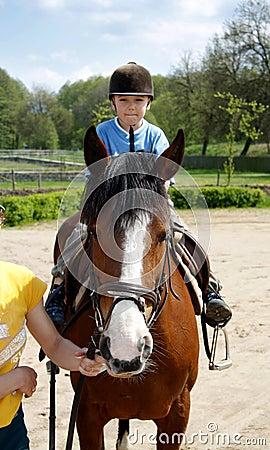 Boy rides on a horse