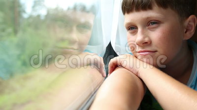 The boy rides in a train. He sits in the coupe and looks out the window stock video footage