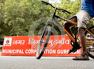 Boy riding bicycle in front of MCG board Editorial Image
