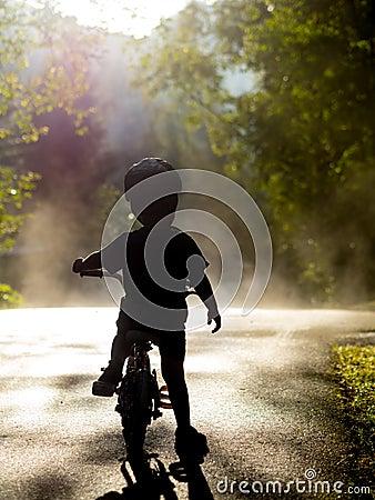 Boy riding bike in mist