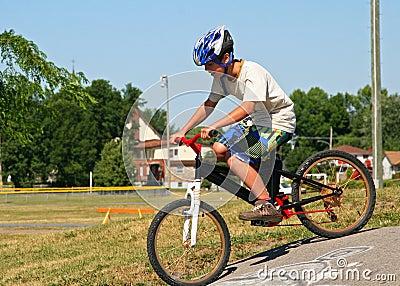 Boy riding bike on a paved driveway