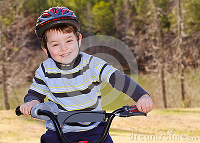 Boy riding bike with safety helmet