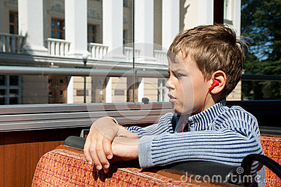 Boy riding on bus listening excursion
