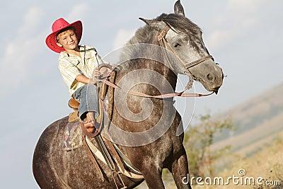 Boy riding a horse on farm outdoors