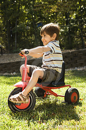 Boy riding tricycle.
