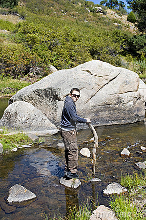Boy in the river by a boulder