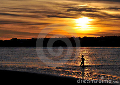 Boy in river at sunset
