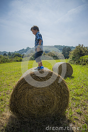 Boy on round hay bale