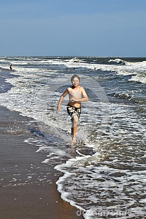 Boy running along the beautiful beach in the waves