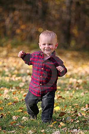 Boy running in autumn leaves