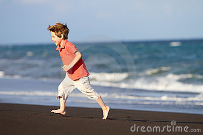 Boy running at black sand beach