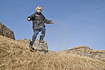 Boy running down a hill at the fortress