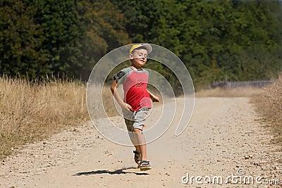 Boy running on dusty road
