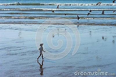 A boy running on the ocean beach