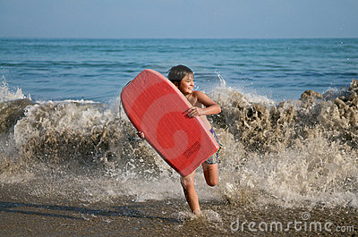 Boy running with surfing board