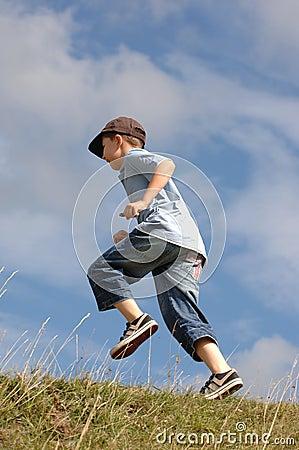 A boy running up a grass hill