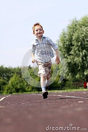 boy runs in a summer park