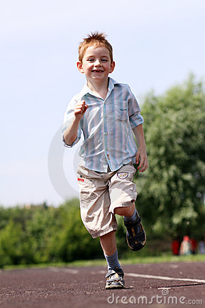 Boy runs in a summer park