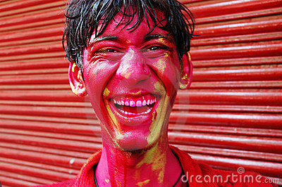 A boy's face smeared with colour.