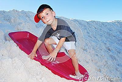 Boy sand sledding