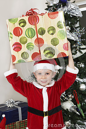 Boy In Santa Claus Outfit Carrying Present On Head