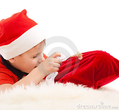 Boy in Santa s hat open christmas bag with gifts