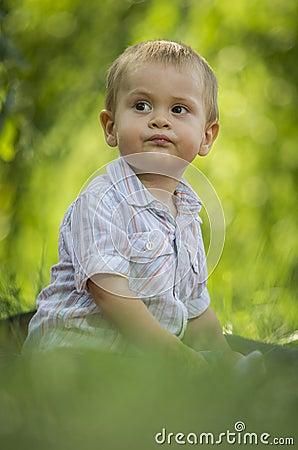 Boy sat in green park