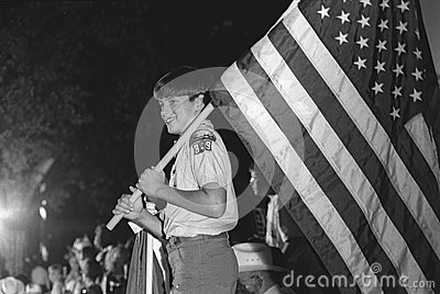 Boy Scout carries the American flag Editorial Image