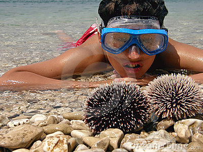 Boy in sea with sea urchins