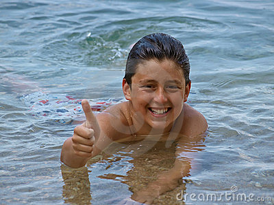 Boy in sea showing thumbs up sign