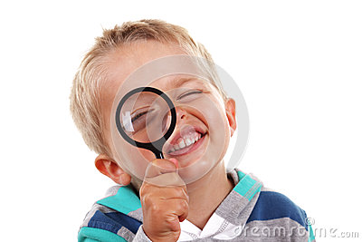 Boy searching with magnifying glass