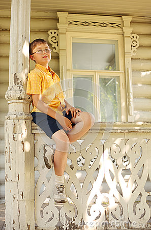 Boy seat on handrails on terrace