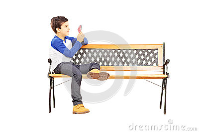 Boy seated on bench and playing cards with imaginary friend