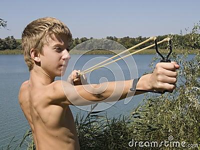 Boy shoots a slingshot