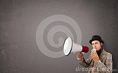 Boy shouting into megaphone on copy space background