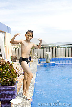 Boy showing his muscle besides swimming pool