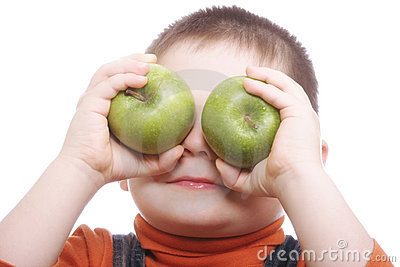 Boy shutting eyes with apples