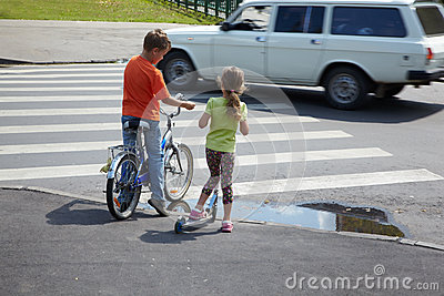 Boy and sister stand before zebra crossing