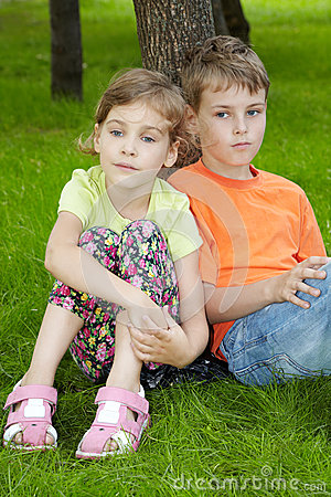 Boy sits on grass, his sister sits next to him