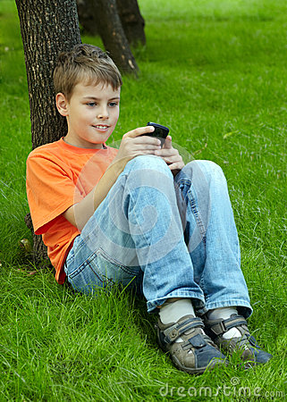 Boy sits on grass plays with electronic game