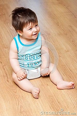 Boy sits on hardwood floor