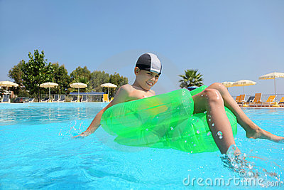 Boy sits on an inflatable arm-chair in pool