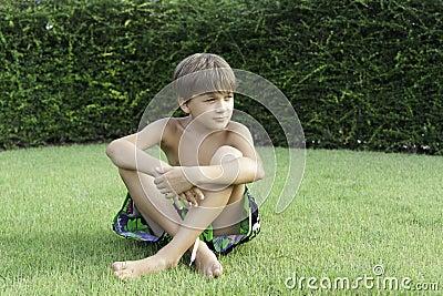 The boy sits on a lawn