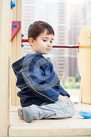 Boy sits on playground