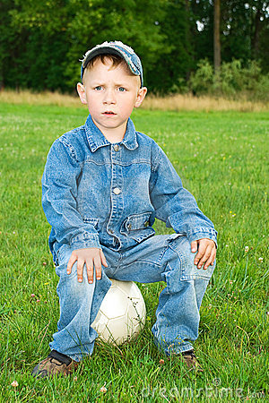 Boy sits on soccer ball