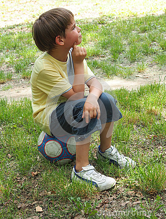 A boy sitting on the ball