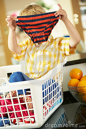 Boy Sitting In Basket Sorting Laundry