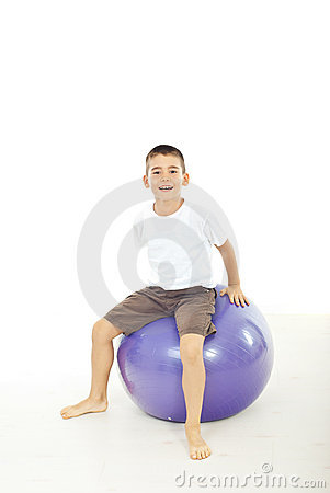 Boy sitting on big ball