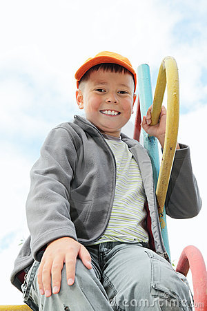 Boy sitting on climbing staircase